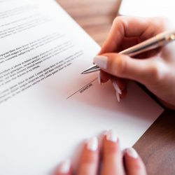 female-hand-signing-insurance-contract-picjumbo-com